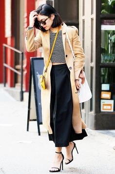 Vanessa Hudgens in a tan coat, striped shirt, black shirt, black sandal heels, yellow bag, and sunglasses