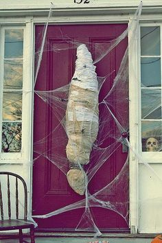 There's a Mummy at the Door Enter, if you dare! Stuff some trash bags with light, moldable filling (think leaves or cotton balls) to create your own mummy. Wrap it up in gauze while shaping out a mummy silhouette and suspend your creation with some crafty cobwebs. from Yahoo! Halloween House of Horror