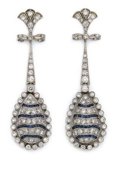Pair of Diamond and Sapphire Pendant-Earrings  Platinum, topped by a stylized fleur-de-lys, supported by a delicate bow, joined by a tapered bar link, suspending a drop-shaped domed panel set with alternating diamond and French-cut sapphire bands, set throughout with 120 round diamonds approximately 2.80 cts., circa 1920, gold posts added later, approximately 7.3 dwt.