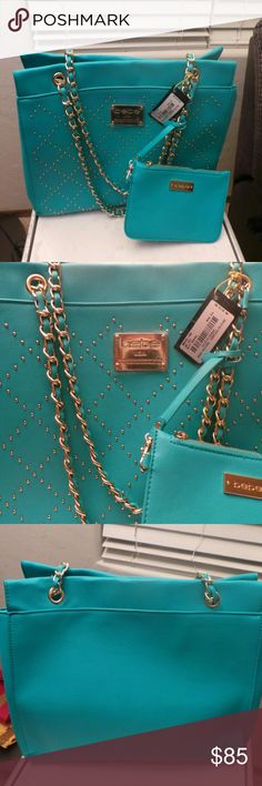Bebe neon teal handbag Beautiful neon teal handbag from Bebe with Gold details in the front and gold and neon teal straps. Green interior, very roomy with a matching wallet.Material: PU exterior, polyester lining 2 Main Compartments 2 Zipper Pockets Inside 2 Accessory Pockets Inside 1 Detachable Accessory Pocket with Zipper Closure Dual Handle style with 9.5'' shoulder drop 4 Metal Cleats at Bottom Care: Wipe with damp cloth Approx: 14''W x 10.75'' H x 4.5'' D Coin purse: 7.25'' W x 4.75'' H…