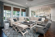 """Traditional family room with walls painted in Clark+Kensington's """"Inspire Awe"""", large beige sectional, wood floors, open concept to the kitchen, and blue and brown patterned rug 