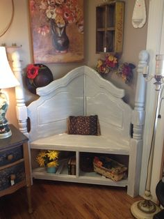 Corner bench made from a queen sized headboard. Extra storage on bottom, perfect for shoes or baskets. Painted in our home-made chalk paint...Based with Country White and topped with a light grey and clear wax.