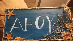 DIY wooden Ahoy sign  Handpainted . Items used : acrylic paint , wooden board ,sea stickers , jute, fisherman net .