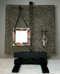 """Style. MM2 """"Style"""" 16"""" x 16"""" x 1/8"""" Woven dried vines, metal, wood, glass, leather and ribbon This mixed media piece combines a rustic feel with an elegant contemporary style. This particular piece can be hung on the wall or placed on a small art easel as shown. (Easel not included.) Creating the glass vase is a very large antique test tube. The picture frame can be filled with your own photograph and vase filled with fresh flowers. What a great way to personalize and give as a gift!."""