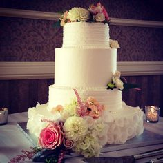 Wedding Cake with various size tiers, White Chocolate Curls, Hydrangea, Roses, & Wild Flowers.
