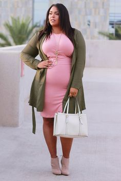 Tanned chocolette in coral sheath dress, olive trench, nude booties w/ eggshell handbag