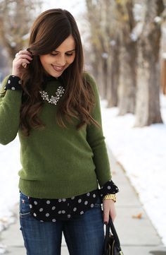 Green sweater, long sleeved print blouse peeking through, denim jeans, pearly statement necklace.