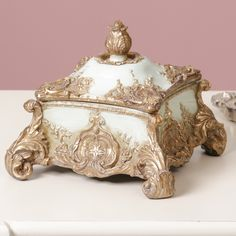 This stunning ornate trinket box is a beautiful addition to any dressing table! Finished in a luxurious shade of turquoise, with contrasting gold detailing; the colours are eye catching and the design is breath taking. With four scrolled feet, the trinket box has delicate leaf and floral detailing, adding to the design of the box. Complete with fully removable lid, the box is suitable for holding rings, bracelets and trinkets. Gift for Her.