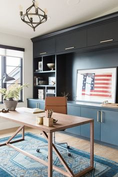 Modern office with open shelving, vintage rug and dark blue cabinets