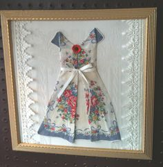 More Thrift Shop art:  Nice frame with old faded picture removed, vintage damask place mat for background, and vintage handkerchief folded origami style into a sweet vintage-style dress!