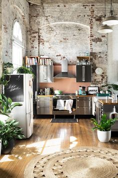 Cool bohemian loft kitchen space. The weathered brick wall and high ceilings add lots of character. Loft kitchen | kitchen ideas | kitchen design | kitchen inspiration | plants (scheduled via http://www.tailwindapp.com?utm_source=pinterest&utm_medium=twpin)