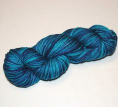 Hand Dyed Fingering Weight 3 ply yarn skein made of Superwash Blue Faced Leicester Wool (BFL) in shades of Turquoise and Blue