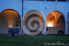Photo taken inside a palace of Treviso in the Veneto region (Italy). In the picture you see, in the foreground, a well that is located in the inner courtyard with lawn of a historic building for exhibitions. The three pillars and their arches that surround the porch, lit by lamps at sunset.