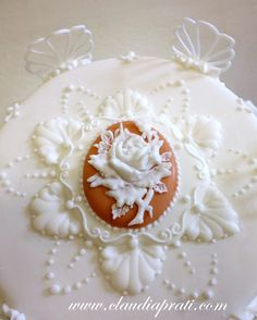 royal icing top. Pressure piped rose. Run out, piping, laces