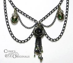 "A sort of ""goth"" style Light weight black metal chain with a tarnished rose with two emerald like crystal gems encased inside of golden scarabs  on either side. The matching earrings are roses made of hand dyed material.   1st place winner of the 2013 Summer Contest ""The stuff of nightmares"". ..."
