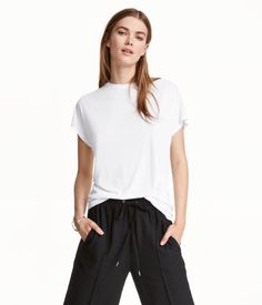 White. Top in soft jersey with a sheen. Slightly looser fit. Cap sleeves and a…