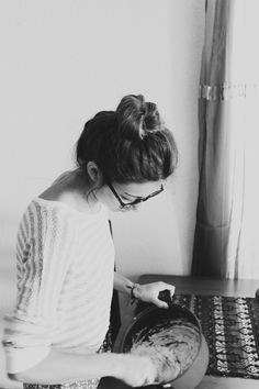 love this timeless look.  statement glasses, floral skirt, high bun, cooking.  cute!