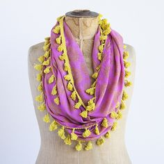 Pink with orange medallion Natural Life print infinity scarf with mustard tassel trim.