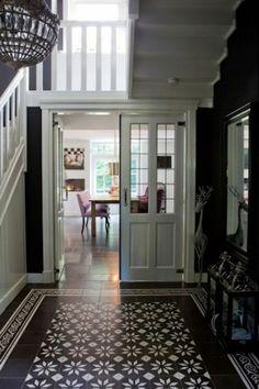 Super mooie hal met donkere wand en wit lakwerk...en natuurlijk maakt de cementtegel het helemaal af!