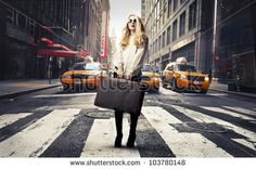 Beautiful woman standing on a crosswalk and holding a suitcase - stock photo