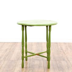 This end table is featured in a solid wood with a lime green paint finish. This cottage chic side table has carved turning legs, cross-stretchers, and a round top. A fun piece that goes great with plants! #cottagechic #tables #endtable #sandiegovintage #vintagefurniture