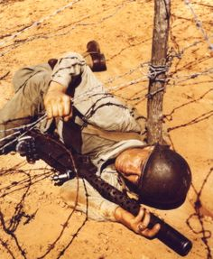 An American soldier holds a .30 cal Browning machine gun as he crawls through a barbed wire entanglement during training exercises, 1940s. (Photo by PhotoQuest/Getty Images)
