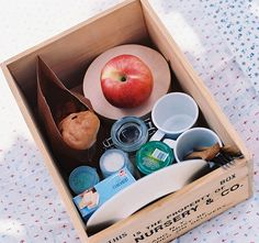 picnic baskets or boxes or crates with picnic foods next to blankets