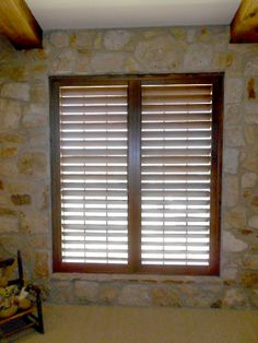 Stained plantation shutters on a rock wall make for a beautiful combination of materials.