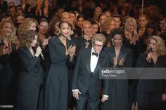 Yves Saint Laurent with Laetitia Casta, actress Catherine Deneuve and models wearing his famous 'le smoking.'