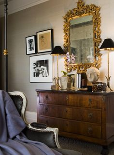 Tall, skinny table lamps and gilded mirror.