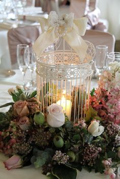 Pretty bird cage centerpiece..dont like the flowers but having pearls, lace, burlap incorporated in it