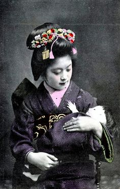 Young Geisha holding a Doll 1910    In this postcard, a Young Geisha from Osaka is cradling a large doll, which is wrapped in the sleeve of her kimono.