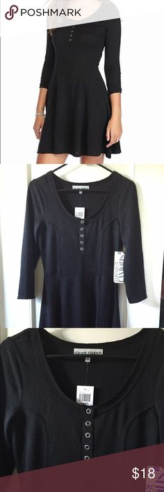 Almost Famous black mid-sleeve skater dress size M This trendy black Almost Famous dress has 3/4 sleeves, 5 silver front snaps, and a flattering skater silhouette.  Fabric is a soft knit poly/span blend. New from Hot Topic with original tags. Almost Famous Dresses Midi