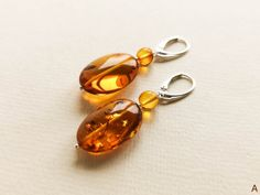 Bright royal cognac color natural amber earrings made from oval shape amber beads and silver findings. These orange color amber resin earrings are a perfect example of how organic amber jewelry can make your life happier. Also a great and very mood-uplifting natural amber gift for your loved ones.