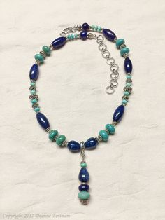 This beautiful necklace in shades of blues is hand crafted from lapis lazuli and turquoise beads with .925 sterling silver. The pendant is removable so the piece can be worn as a string of beads. This necklace is 18.5 in length and is adjustable to 23.