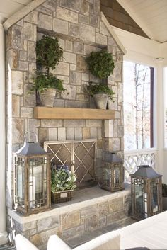This OUTDOOR FIREPLACE is housed in a screened-in porch, and look how awesome the stonework is! I also like the ivy plants in pots that match the fireplace, as well as the metal/glass lanterns. Very tasteful.Like the recessed area on fireplace for tv Fireplace Screens, Home Fireplace, Fireplace Design, Fireplace Mantels, Fireplace Stone, Mantles, Fireplace Ideas, Fireplace Doors, Unused Fireplace