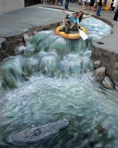 STREET ART UTOPIA. A Photo Story About the Sea in the Name of Street Art. Man and woman in a raft. Sidewalk drawing of rafting down a river towards a crocodile. Credit: Julian Beever