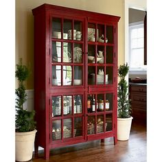 Rojo Red Tall Cabinet  | Crate and Barrel Stately storage. This sizable piece has four glass-paned doors, opening to five fixed shelves. Umber overtones add depth of character to the rich red finish.