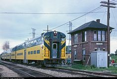 """A CNW """"Scoot"""" commuter train rolls through Deval Tower which protects CNW and Soo Line's crossing on the northwest side of Chicago. This train is on the northwest line, coming into Des Plaines from Harvard, IL. While yellow and green dominated in 1979, hints of RTA blue was on the horizon, with Metra to follow."""