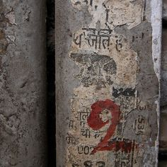 artpropelled:  Xavier Phelp       This original fine art archival print is one of a series taken in a bustling, but run down, area of Delhi, India. The remnants of faded paper and the red painted number on a weathered wall create a fascinating and mysterious composition.