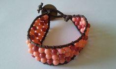 Bracelete trabalhado em bolinhas nas cores marrom, rosa e branco e acabamento com botão marrom vintage.Tamanho:22 cmpeso pena