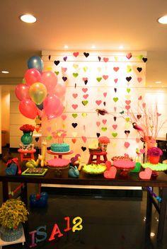 Festa teen neon com muitas cores para menina de 12 anos. A cortina de corações funciona como backdrop e é bem fácil de reproduzir em casa. Lindo, não é?