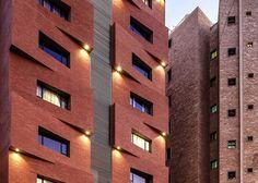 Una facciata divisa in segmenti ad angolo crea un forte modello di luci e ombre in tutta la parte anteriore di questo mattone condominio in Kuwait da studio di architettura locale Studio Toggle.