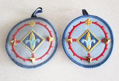 Set of two boy cub scout advancement patches. A compass patch with pins. Measurement: 3 inches in diameter. Condition: There's some fading to the one. A little bit of discoloration.