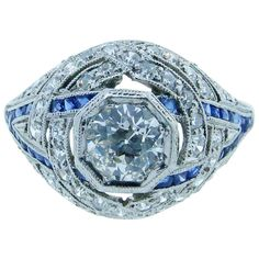 Exquisite Art Deco Diamond Ring. Lovely handmade platinum mount Art Deco ring bead set in the center with a round European cut diamond weighing approximately .65cts. grading VS clarity I color. The mill grained mount is set in a swirl design with 47 round European cut diamonds totaling an additional .55cts. and 32 fancy shape faceted natural blue sapphires. c 1920