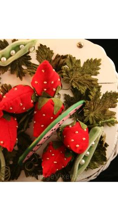 Tossed vintage strawberries atop a vintage purse. The pea pod is gorgeous. From the Vintage Vixen
