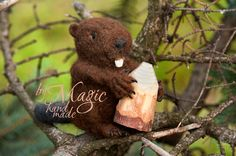 Little felted beaver holding small piece of wood.
