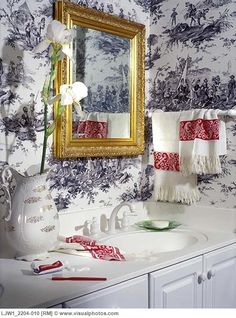 Black and white toile wallpaper, gold framed mirror, white fringed towels with Swedish red borders, white corian counters