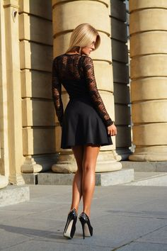 Stunning long legged blonde in a little black dress and towering studded platform high heels