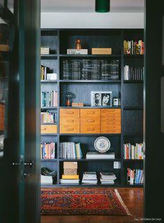 Detalhe da estante  de madeira da sala de estar recheada de livros e coleções do morador.